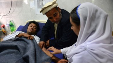 A Pakistani health worker treats an injured student at a hospital a day after an attack by Taliban militants at an army-run school in Peshawar.