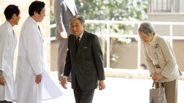 Emperor Akihito arrives at a hospital for treatment in 2012, accompanied by Empress Michiko.
