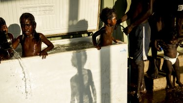Children play in a fridge in Perederr after fleeing the violence-struck community of Wadeye, Northern Territory.