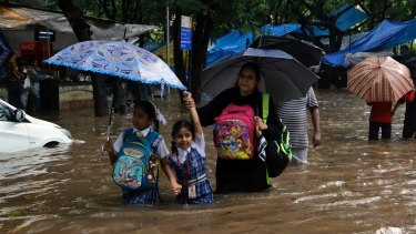 School children wade through a waterlogged street in Mumbai on Tuesday.