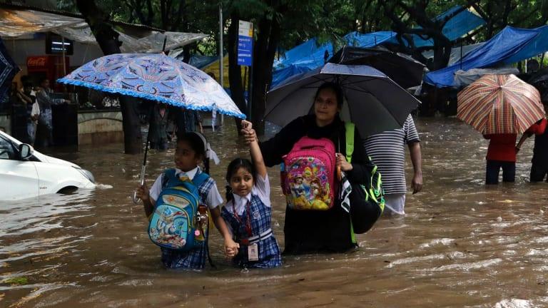 School children wade through a waterlogged street in Mumbai on Tuesday.
