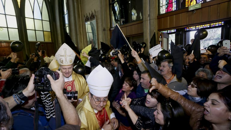 Protestors shout as bishops and priests enter the cathedral in Osorno.