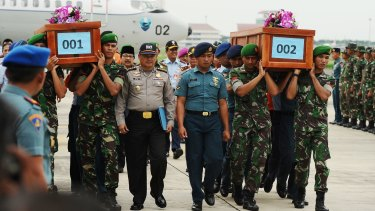 Indonesian soldiers carry coffins containing victims of the AirAsia crash at the Indonesian Air Force Military Base, Surabaya.