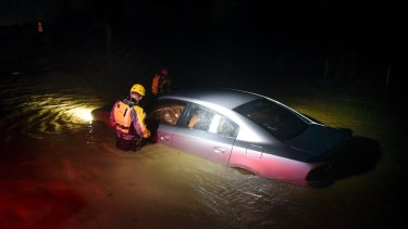 Rescuers investigate an empty flooded car during the passage of Hurricane Irma through the island in Fajardo, Puerto Rico.