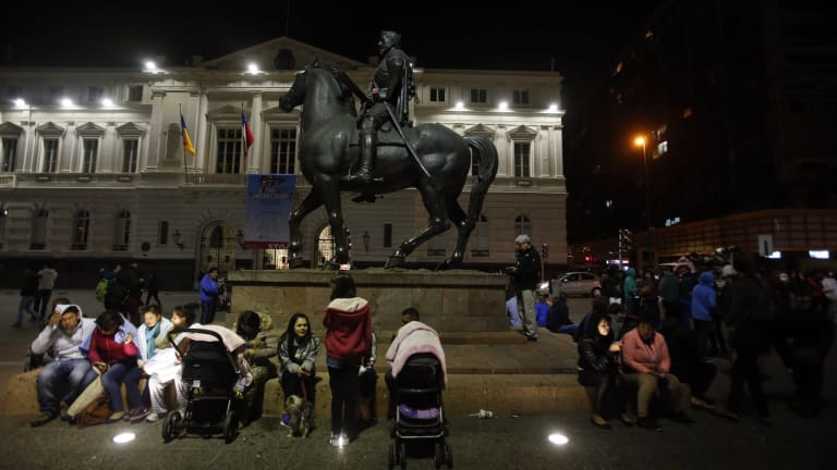 Residents sit in Santiago's main square after a powerful earthquake hit Chile's northern coast causing buildings to sway in the capital.