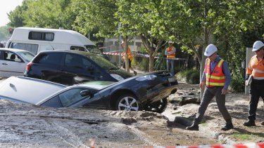 Cars swallowed by a sinkhole caused by flooding in Port Melbourne.