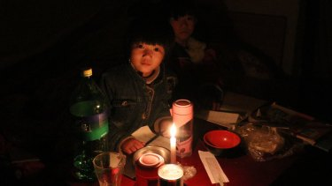 """""""My hands are OK but my feet are cold a little bit,"""" says Xu Yuanyuan, 7, who is trying to study by candlelight."""