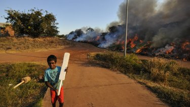 A cricket game is interrupted as fire takes over Minmarama Park community in Darwin, Northern Territory.