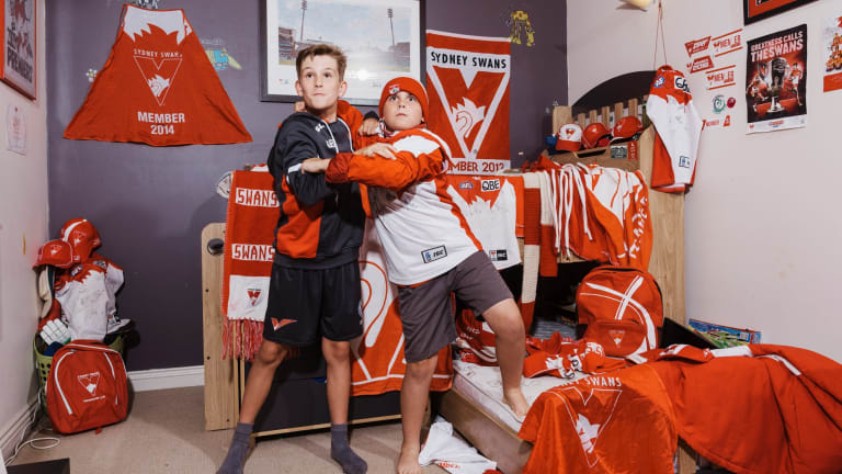 Brothers Ryan (left) and Jude O'Keefe show off the red and white colours of their team, the Sydney Swans.