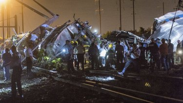 Rescue workers search for victims in the wreckage of a derailed Amtrak train.