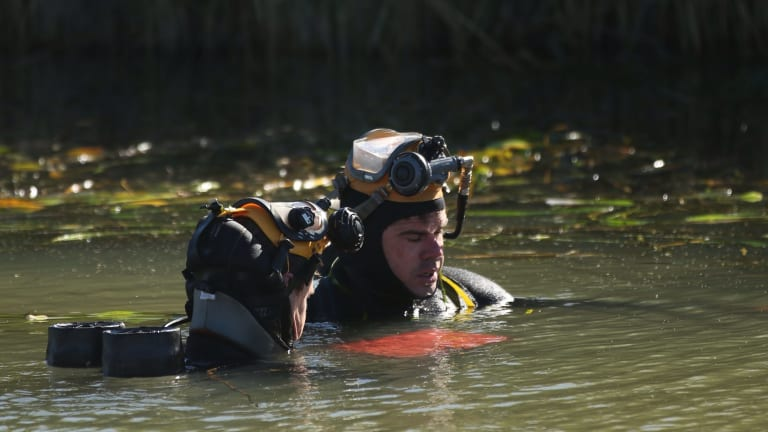NSW police divers hold what appears to be a laptop submerged in an irrigation canal near Leeton, during their search for Stephanie Scott.
