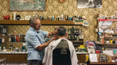 Barber Angelo Perri keeps busy at Paris Style Hairdresser, which looks like a perfectly preserved time capsule from the mid-1960s, in Cabramatta.