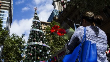 Not the centre of attention: A mourner passes the Martin Place Christmas tree.