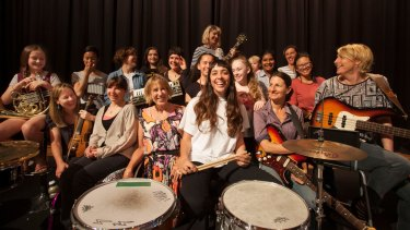 Drummer Bree van Reyk, pictured in white T-shirt in the middle, is assembling a massive girl rock band featuring young local female musicians.