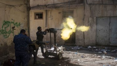 Policemen fire towards Islamic State positions in on the western side of Mosul, Iraq.