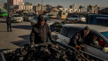 Sellers negotiate the price of raw coal with potential customers in a car at the Shar Khad market in Ulaanbaatar, Mongolia.
