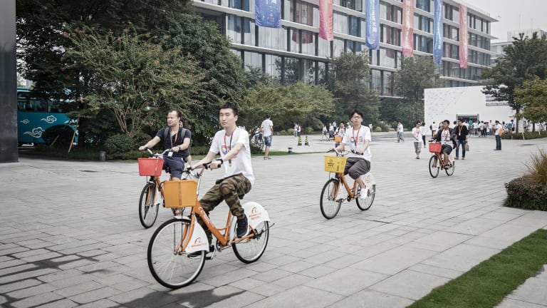 Employees ride their shared bikes though the grounds at the Alibaba head quarters in Hangzhou, China.
