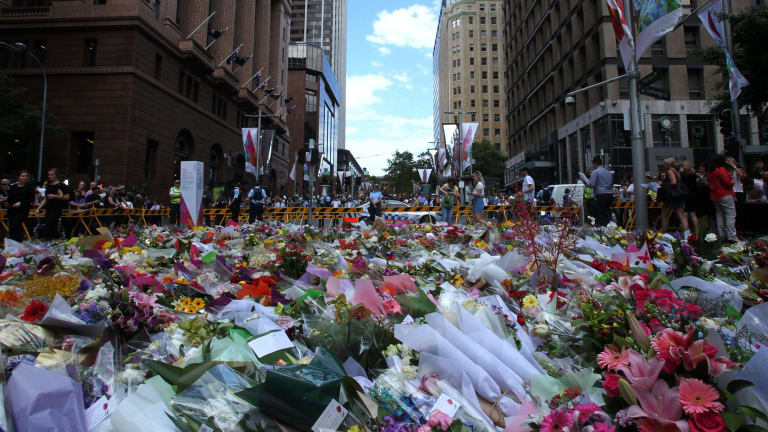 Respectful quiet: People stop to place flowers at Martin Place.
