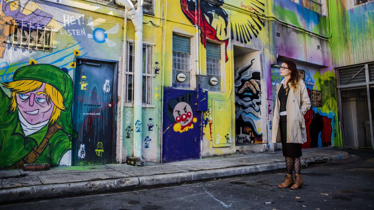 Impact Comics employee Jaisun admires the street art in Tocumwal Lane. The new agenda proposes  making Civic's laneways safer, and sites for art and music.
