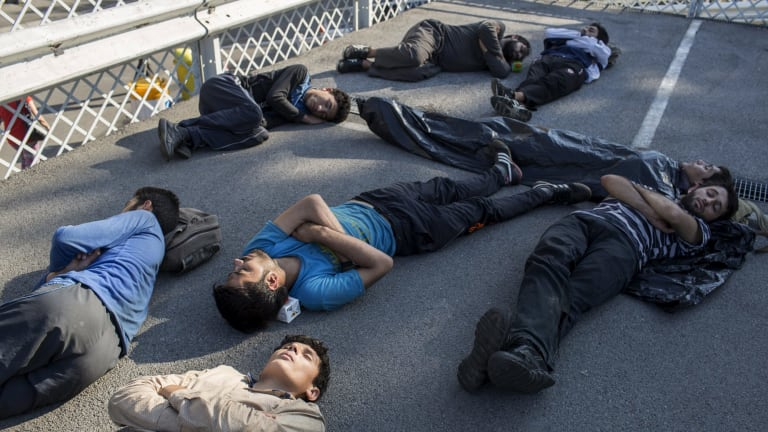 Migrants sleep at a parking lot near Belgrade's main bus and train station, in Serbia on Thursday.