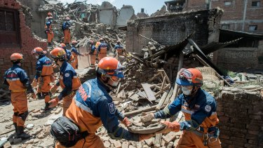 A Japanese disaster relief team remove debris from a collapsed building.