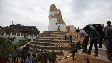 Volunteers work to remove debris at Dharahara Tower following the earthquake in Kathmandu, Nepal, on April 25.