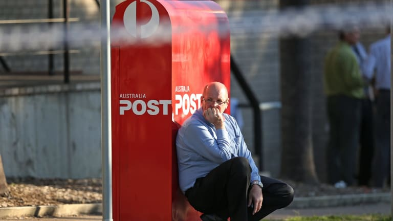 A man leans against an Australia Post letterbox at the scene of a shooting outside Warners Bay Post office on Wednesday afternoon.