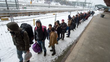 Refugees walk to a chartered train at the railway station of Passau, Germany on Tuesday. Migrants and refugees continue to arrive in Germany to seek for asylum.