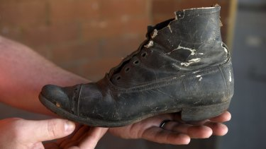 The boot was uncovered behind the fireplace at Children's Court in Surry Hills, more than a century after it was hidden.