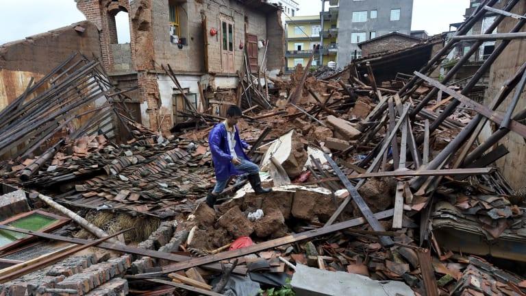 A man walks past damaged houses following Typhoon Nepartak hit Putian city in southeast China's Fujian province.