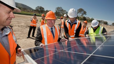 ACT Greens MLA Shane Rattenbury, Planning Minister Mick Gentleman and Daniel Radford lifting panels at the Williamsdale solar farm.