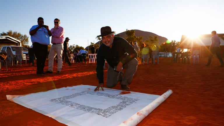 Noel Pearson signs the canvas upon which the Uluru statement was painted. The Turnbull government rejected the statement's recommendations.
