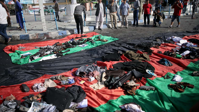 Afghans look at property left behind by victims of an explosion that struck a peaceful protest march.