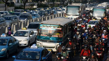 Cars, buses and motorbikes caught in Jakarta's commuter crawl.