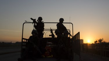 Soldiers patrol on a highway near the Mare Complex slums at sunrise in Rio de Janeiro, on Sunday.