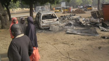 Children stand near the scene of a suicide bomb attack in Potiskum.