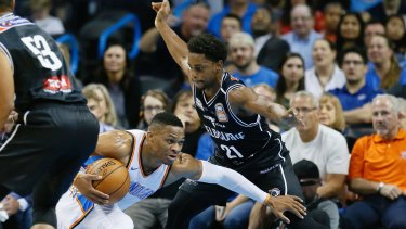 Oklahoma City Thunder guard Russell Westbrook (left) falls as he drives around Melbourne United's Casper Ware.