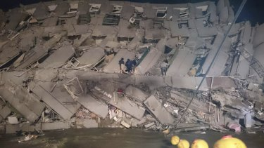 Rescuers entering a collapsed office building in Tainan.