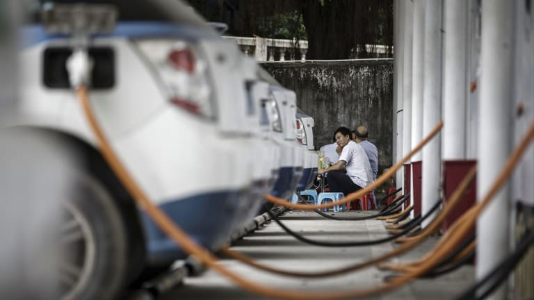 Charging cables connect to a row of electric taxis in Shenzhen, China.