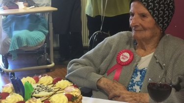 Maria Stella Costa marks her 100th birthday with a cake - one of three - and a glass of red.