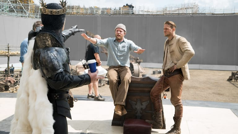 (From left) Jude Law as Vortigern, director Guy Ritchie and Charlie Hunnam on the set of <i>King Arthur</i>.
