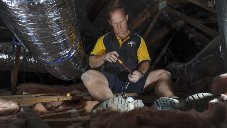 Electrician Paul Callaway in the roof space of a home in Weston. He says he has no doubt been in Mr Fluffy homes during his 20-year career.