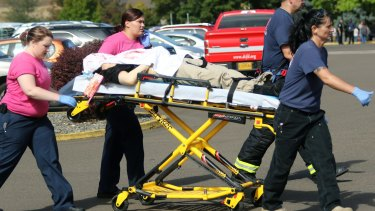 Authorities carry a shooting victim away from the scene after a gunman opened fire at Umpqua Community College in Roseburg earlier this month.