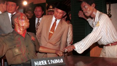 Then Indonesian president B.J. Habibie, centre, inspects a diorama depicting the murder of an Indonesian army general by alleged communists during a coup attempt in 1965. The coup attempt sparked the 1965 massacres of alleged communists.