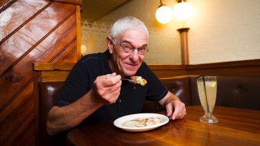 """""""The Original Pancake Man"""" Philip Barton eating pancakes that he made, topped with whipped butter and maple syrup."""