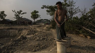 Ko Bo Bo collects what's left of the water in a small pond his family uses as a water source in Dala, Burma.