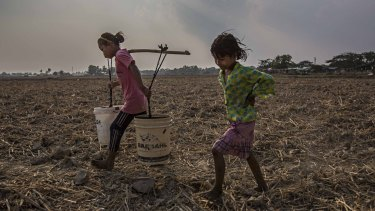 Ma Moe Thu, 11, and Zin Mar Win, 7, carry buckets of clean water across dry rice paddy fields back in Dala, a township south of Yangon, Burma.