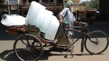 An Indian worker uses a ricksahw to transport ice from an ice factory in Amritsar.