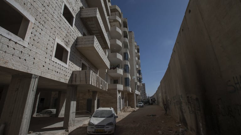 A building under construction next to Israel's separation wall in the Kufr Aqab neighbourhood of Jerusalem. Planned demolitions threaten to drive people out of their homes.