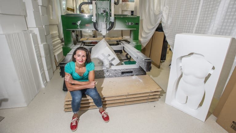 Entrepreneur Hollie Bell with her CNC machine and one of her torsos.